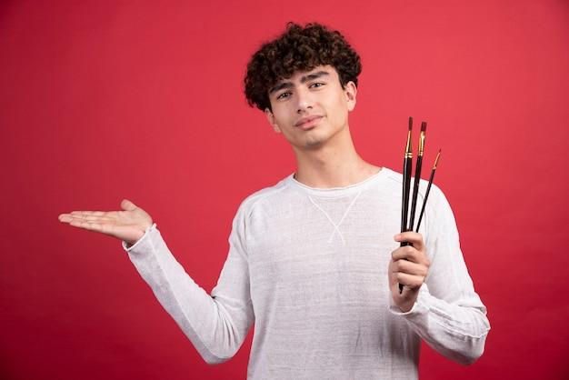 Jeune peintre au pinceau debout.