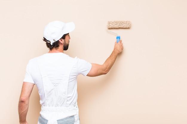 Jeune peintre barbu peignant un mur avec un rouleau à peinture
