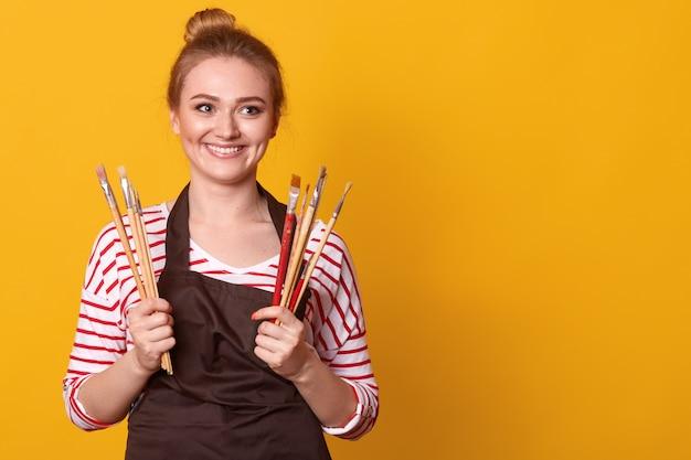 Jeune peintre caucasien travaillant. jeune femme créative peignant sur toile dans son atelier.
