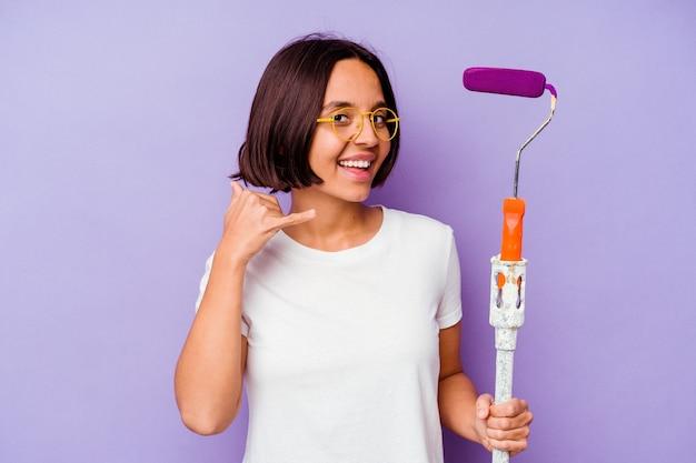 Jeune peintre métisse femme tenant un bâton de peinture isolé sur fond violet montrant un geste d'appel de téléphone mobile avec les doigts.