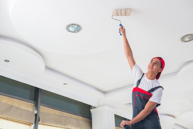Jeune peintre peignant le plafond en concept de construction