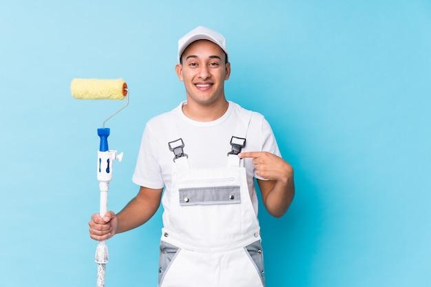Jeune peintre professionnel homme latin personne isolée pointant à la main vers un espace de copie de chemise, fier et confiant