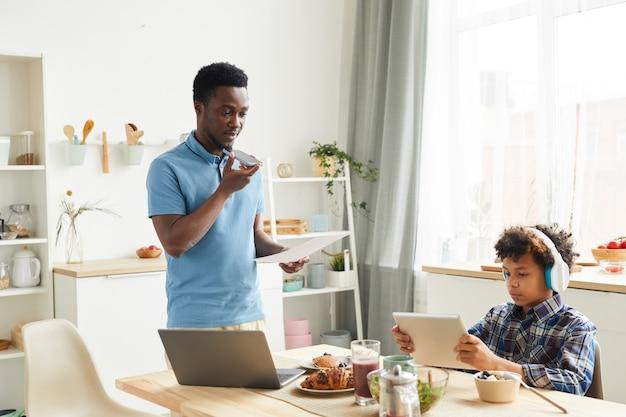Jeune père africain parlant au téléphone et examinant des documents qu'il travaille à la maison pendant que son fils joue à des jeux sur tablette numérique dans la cuisine
