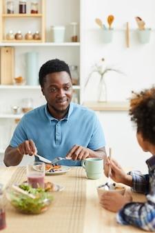 Jeune père africain prend le petit déjeuner avec son fils à la table dans la cuisine, ils sourient et parlent