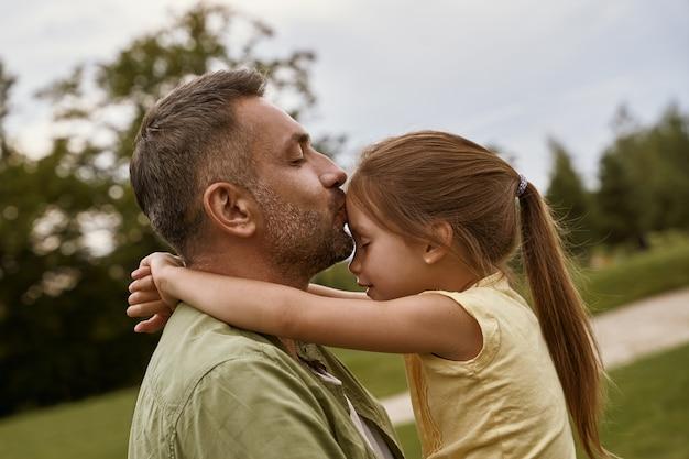 Jeune père aimant embrassant sa mignonne petite fille au front tout en passant du temps ensemble