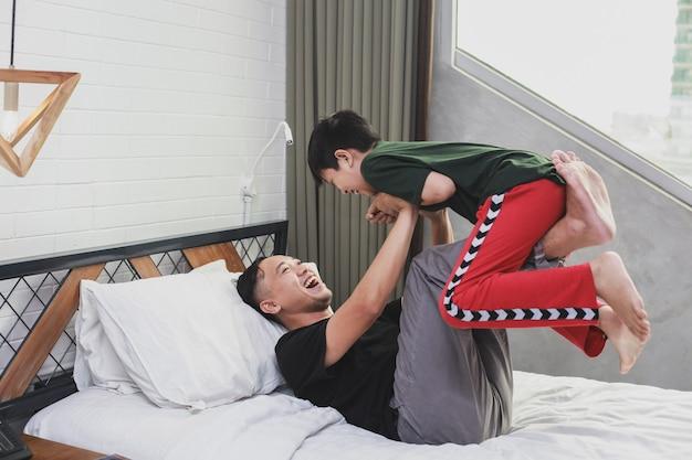 Jeune père asiatique jouant avec son fils sur le lit
