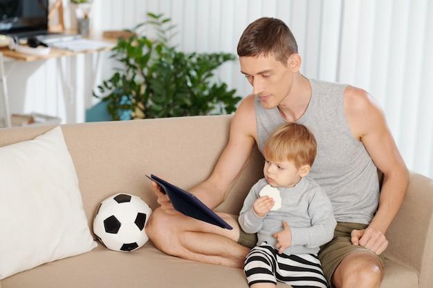 Jeune père assis sur un canapé avec son petit fils et regardant des dessins animés ensemble sur une tablette numérique