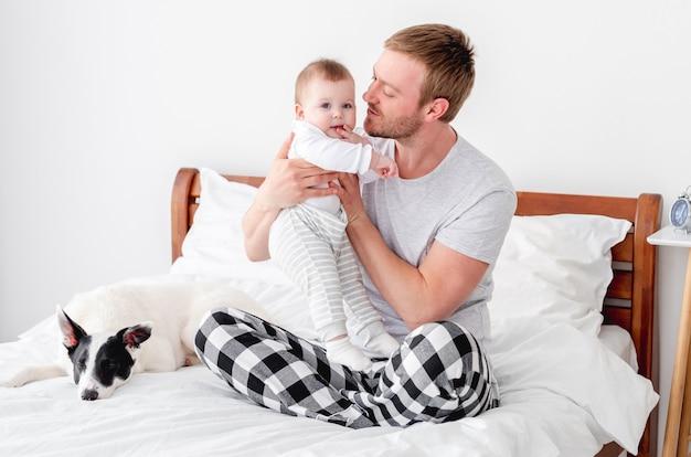 Jeune père assis dans le lit avec un petit fils et un chien mignon dans la pièce avec la lumière du soleil et serrant son petit garçon dans ses bras. homme restant dans la chambre avec son enfant et son animal de compagnie. mec avec enfant et chien le matin