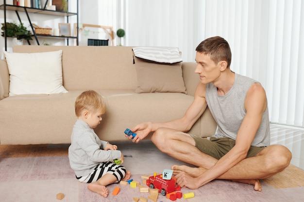 Jeune père assis par terre avec son enfant et jouant avec des blocs de couleur ensemble dans la pièce