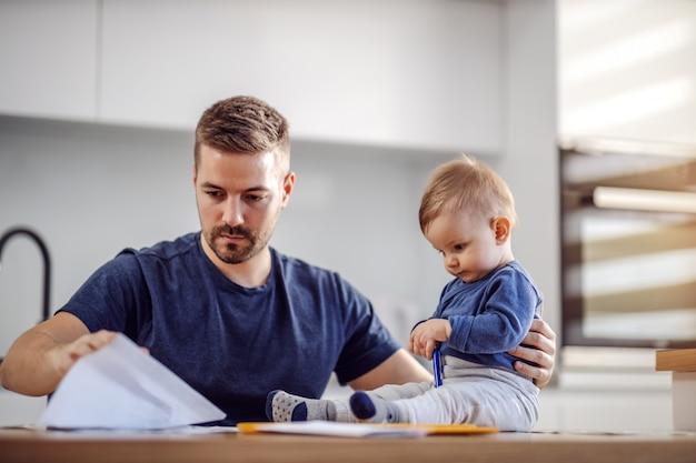 Jeune père barbu attrayant assis à table à manger avec son adorable fils bien-aimé et payer ses factures en ligne. son garçon tenant un stylo et essayant de l'aider.