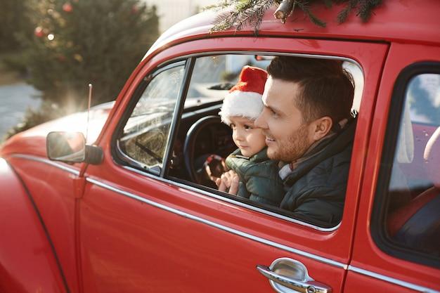 Jeune père barbu avec joli fils en chapeau de père noël posant à l'intérieur de la voiture rétro rouge