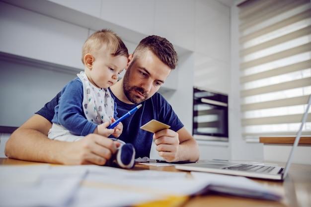 Jeune père barbu pensif barbu tenant une carte de crédit et se préparant à payer les factures par ordinateur portable. son petit assistant assis sur la table.