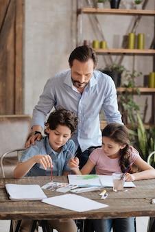 Jeune père barbu serrant ses adorables enfants par derrière et les regardant peindre une aquarelle