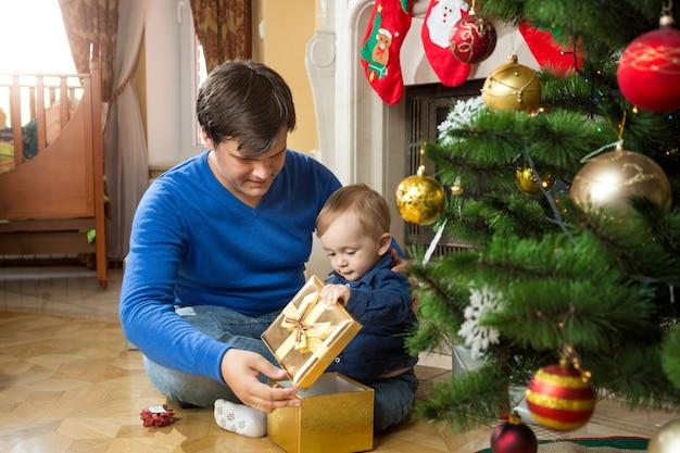 Jeune père et bébé mignon ouvrant des cadeaux de noël sur le sol