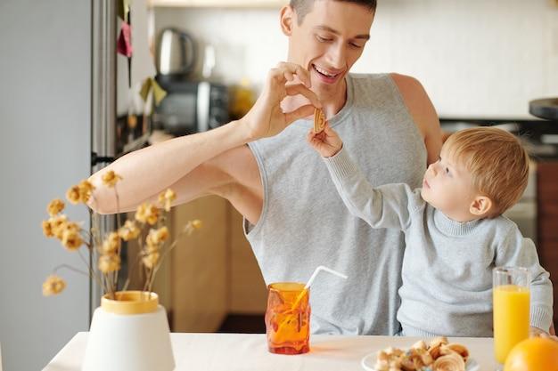 Jeune père donnant des biscuits à son petit fils et ils boivent du jus ensemble dans la cuisine