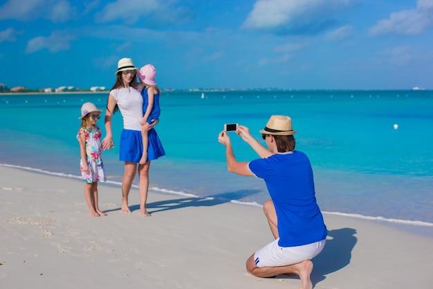 Jeune père faisant la photo sur le téléphone de sa famille à la plage