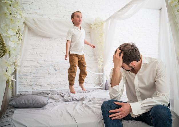 Jeune père fatigué est assis sur le bord du lit