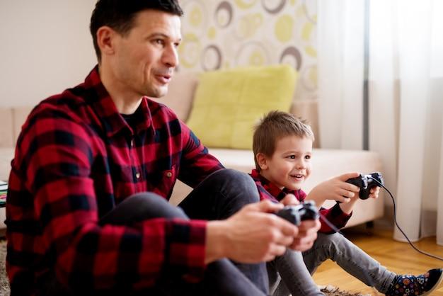 Jeune père et fils excités joyeux dans la même chemise rouge jouant à des jeux de console avec des manettes dans un salon lumineux.