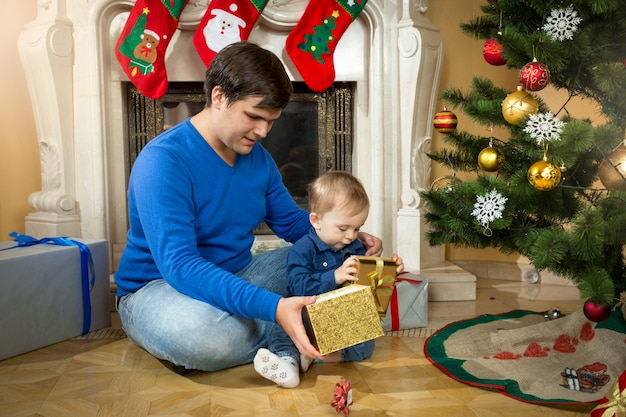 Jeune père et fils mignon de bébé ouvrant des cadeaux de noël sur le plancher au salon