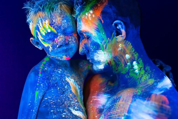 Jeune père et fils. peint avec de la peinture fluorescente utilisant la lumière uv