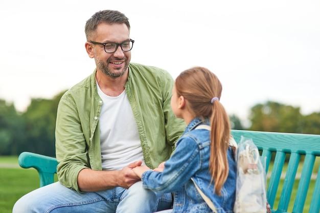 Jeune père gai et sa petite fille mignonne parlant alors qu'il était assis sur le banc, passant du temps