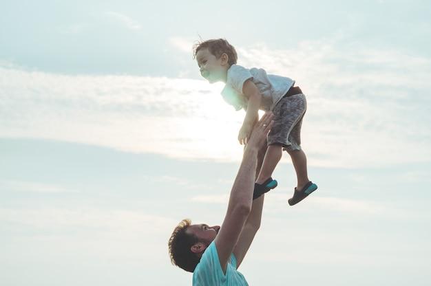Le jeune père jette son mignon et petit fils à l'air frais. fête des pères, père et son fils bébé garçon jouant et étreignant à l'extérieur.