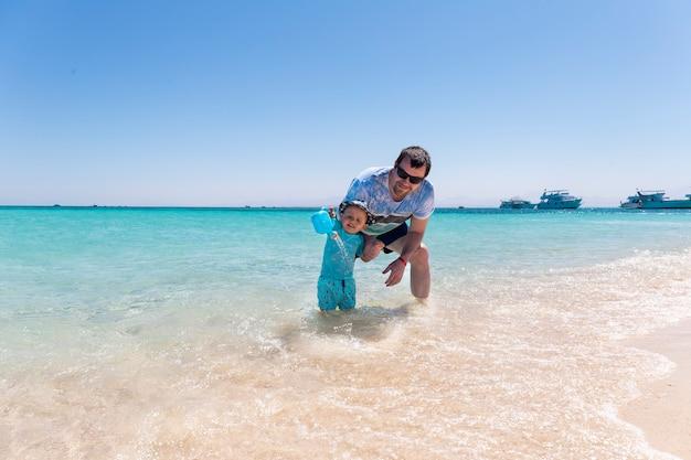 Un jeune père joue sur la plage avec son petit bébé dans la mer. petit garçon joue avec un arrosoir au bord de la mer