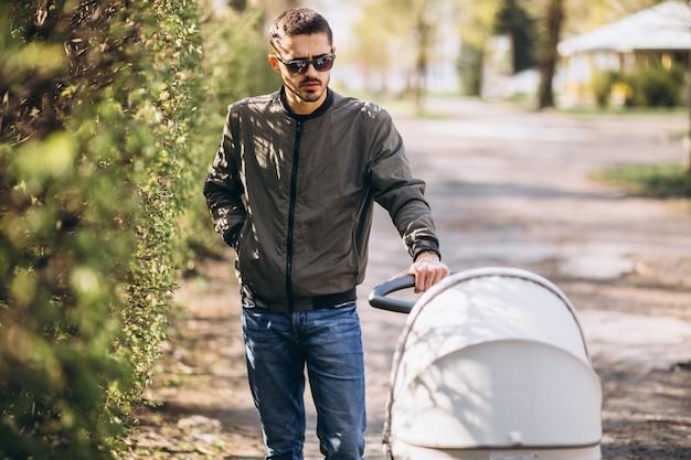 Jeune père marchant avec landau dans le parc