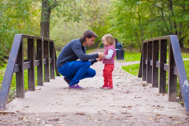 Jeune père marchant avec sa petite fille en automne parc