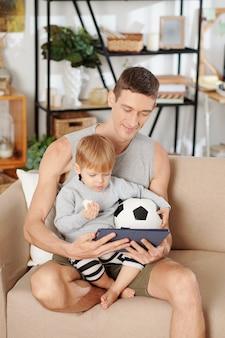 Jeune père montrant des programmes éducatifs sur tablette numérique à son petit fils alors qu'ils étaient assis sur un canapé