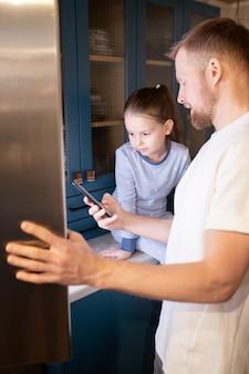 Jeune père montrant à sa jolie petite fille comment réguler la température dans le réfrigérateur tout en passant du temps ensemble à la maison