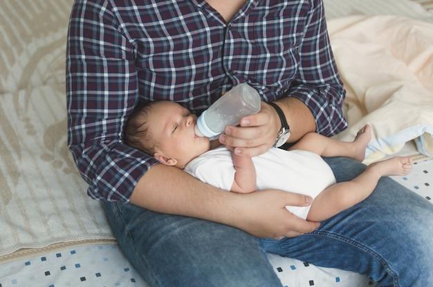 Jeune père nourrissant un bébé mignon avec du lait au biberon