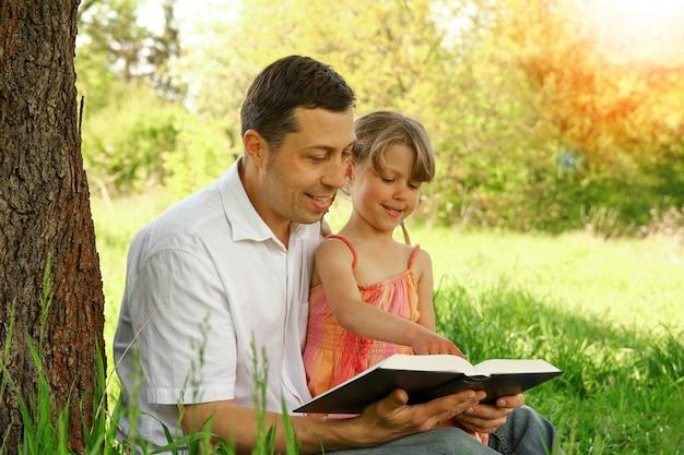 Jeune père avec une petite fille lisant la bible