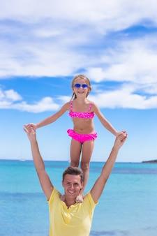 Jeune père et petite fille s'amuser pendant des vacances à la plage tropicale