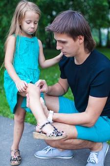 Un jeune père a pitié de sa petite fille qui lui a mal à la jambe