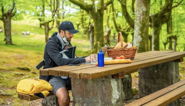 Un jeune père de race blanche télétravail assis à une table de pique-nique avec ordinateur dans les bois