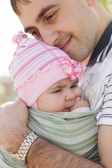 Jeune père avec sa fille en écharpe, printemps en plein air