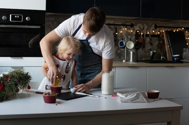 Jeune père et sa jolie petite fille font joyeusement des sucettes de noël ensemble. la cuisine est décorée pour le nouvel an. activité de loisirs d'hiver traditionnelle en famille