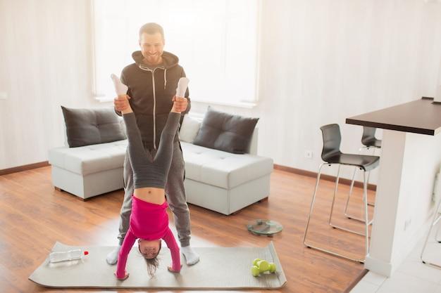 Le jeune père et sa mignonne petite fille s'entraînent à la maison. push-up renversé. enfant mignon est debout sur les mains. ils portent des vêtements de sport et font des exercices