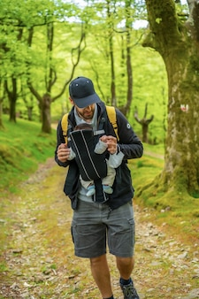 Un jeune père avec un sac à dos jaune marchant avec le nouveau-né dans le sac à dos sur un chemin dans les bois