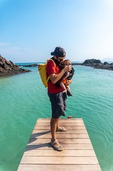 Un jeune père avec son fils sur la passerelle en bois au bord de la mer sur l'isla de lobos, au large de la côte nord de l'île de fuerteventura, îles canaries. espagne