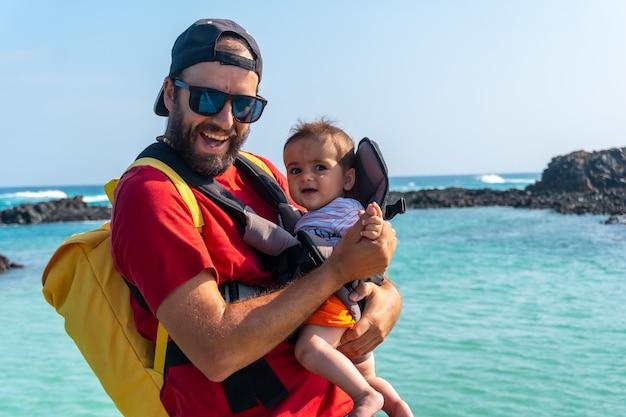 Un jeune père avec son fils en vacances sur la passerelle en bois au bord de la mer sur l'isla de lobos, au large de la côte nord de l'île de fuerteventura, aux canaries. espagne