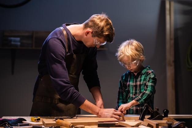 Un jeune père et son petit fils fabriquent un jouet en bois dans un atelier de menuiserie.