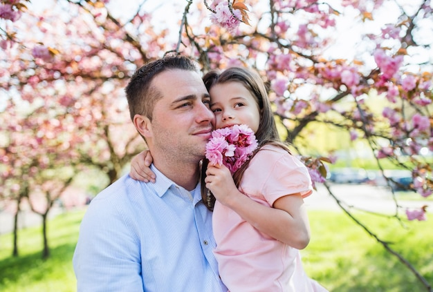 Un jeune père tenant une petite fille à l'extérieur dans la nature printanière.
