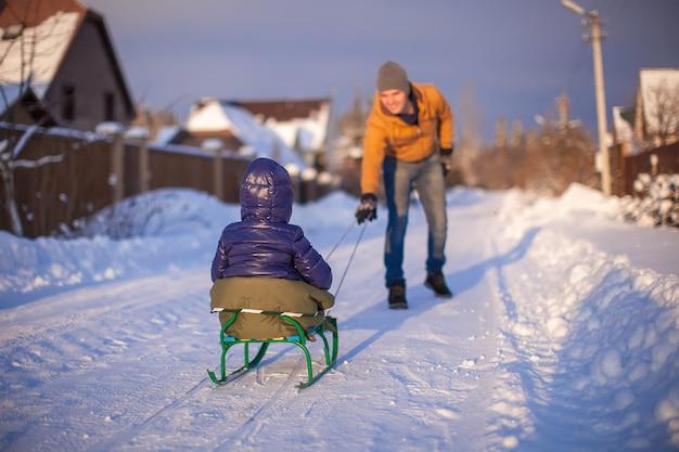 Jeune père en traîneau sa petite fille sur un traîneau dans la neige en plein air