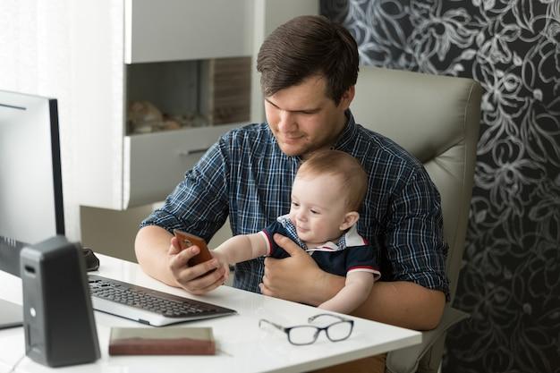 Jeune père travaillant au bureau et prenant soin de son bébé