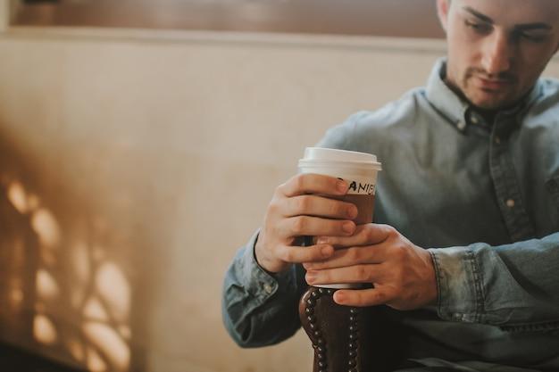 Jeune personne adulte tenir une tasse de café en papier à emporter dans les mains et boire du café au café