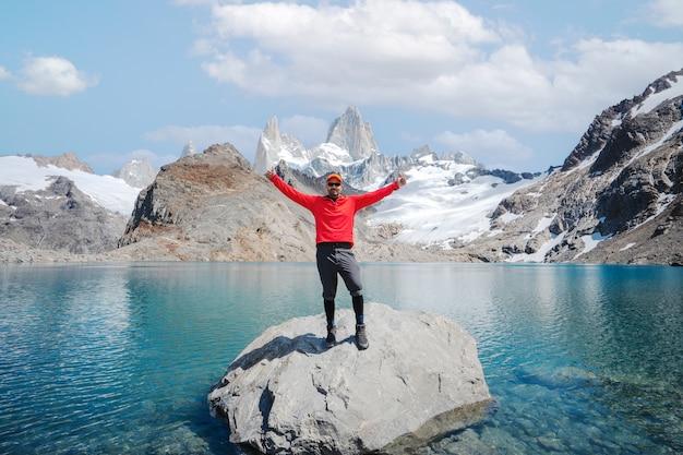 Jeune personne debout sur la laguna de los tres en vue de fitz roy à bras ouverts pour célébrer