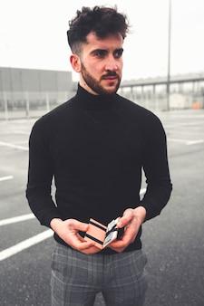 Jeune personne vérifiant un portefeuille avec des euros et des cartes