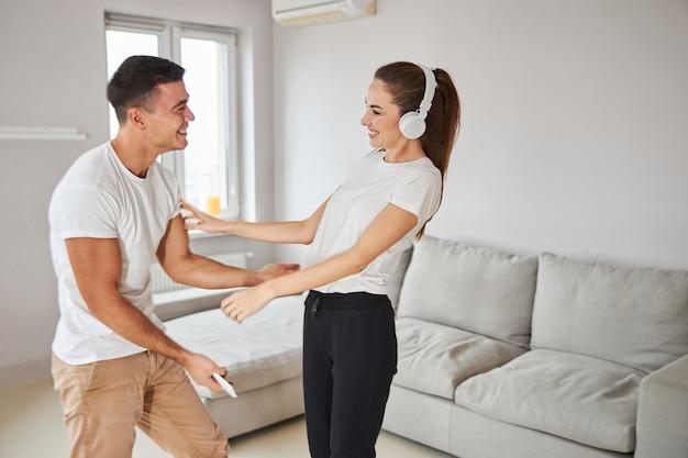 Jeune petit ami et petite amie dansant sur de la musique à la maison